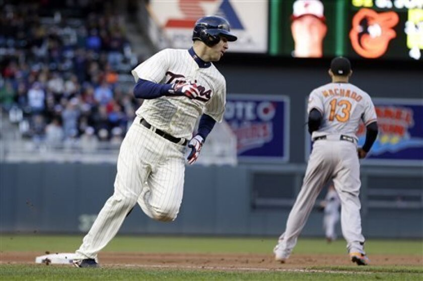 Minnesota Twins' Joe Mauer, left, rounds third on his way home to score on a two-run single by Justin Morneau off Baltimore Orioles pitcher Steve Johnson in the fourth inning of a baseball game on Saturday, May 11, 2013, in Minneapolis. (AP Photo/Jim Mone)