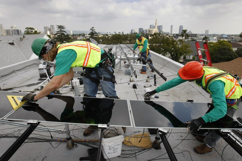SolarCity employees install solar panels on a West Los Angeles home in 2009. Whole Foods Markets has struck deals with SolarCity and NRG to install rooftop solar energy systems at up to 100 of its stores and distribution centers.