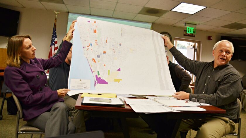 Mayor Catherine Blakespear and No on T Spokesman Bruce Ehlers hold up a zoning map of Encinitas at the Housing Element Update Task Force meeting on Feb. 23.