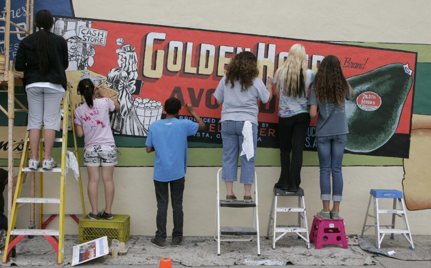 Volunteers participate in the Mural-in-a-Day event earlier this month in Vista. Artist Art Mortimer, who grew up in Vista, designed the mural, which was painted on the side of Urbn Pizza on Main Street. The work depicts the logo of Golden Hours Avocados company from the city's past.