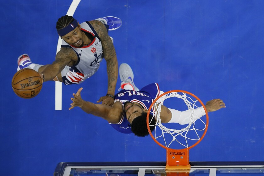 Washington Wizards' Bradley Beal, left, goes up for a shot against Philadelphia 76ers' Tobias Harris during the second half of Game 5 in a first-round NBA basketball playoff series, Wednesday, June 2, 2021, in Philadelphia. (AP Photo/Matt Slocum)