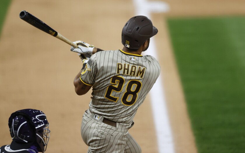 San Diego Padres' Tommy Pham follows the flight of his three-run home run off Colorado Rockies relief pitcher Wade Davis in the ninth inning of a baseball game Friday, July 31, 2020, in Denver. (AP Photo/David Zalubowski)