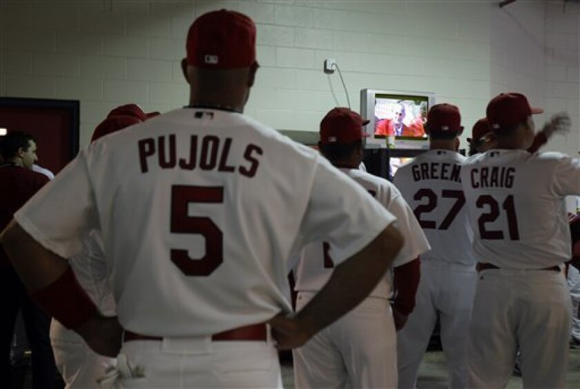 St. Louis Cardinals first baseman Albert Pujols (5) and teammates watch a television monitor under the stadium showing former Cardinals great Stan Musial as he is introduced during festivities before the start of an opening day baseball game against the San Diego Padres, Thursday, March 31, 2011, i