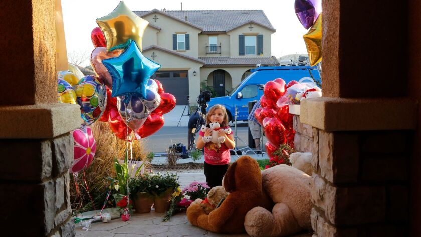 Neighbor Rilee Unger, 3, plays with a toy after dropping off a couple of herteddy bears on the porch of a home where police arrested David and Louise Turpin.