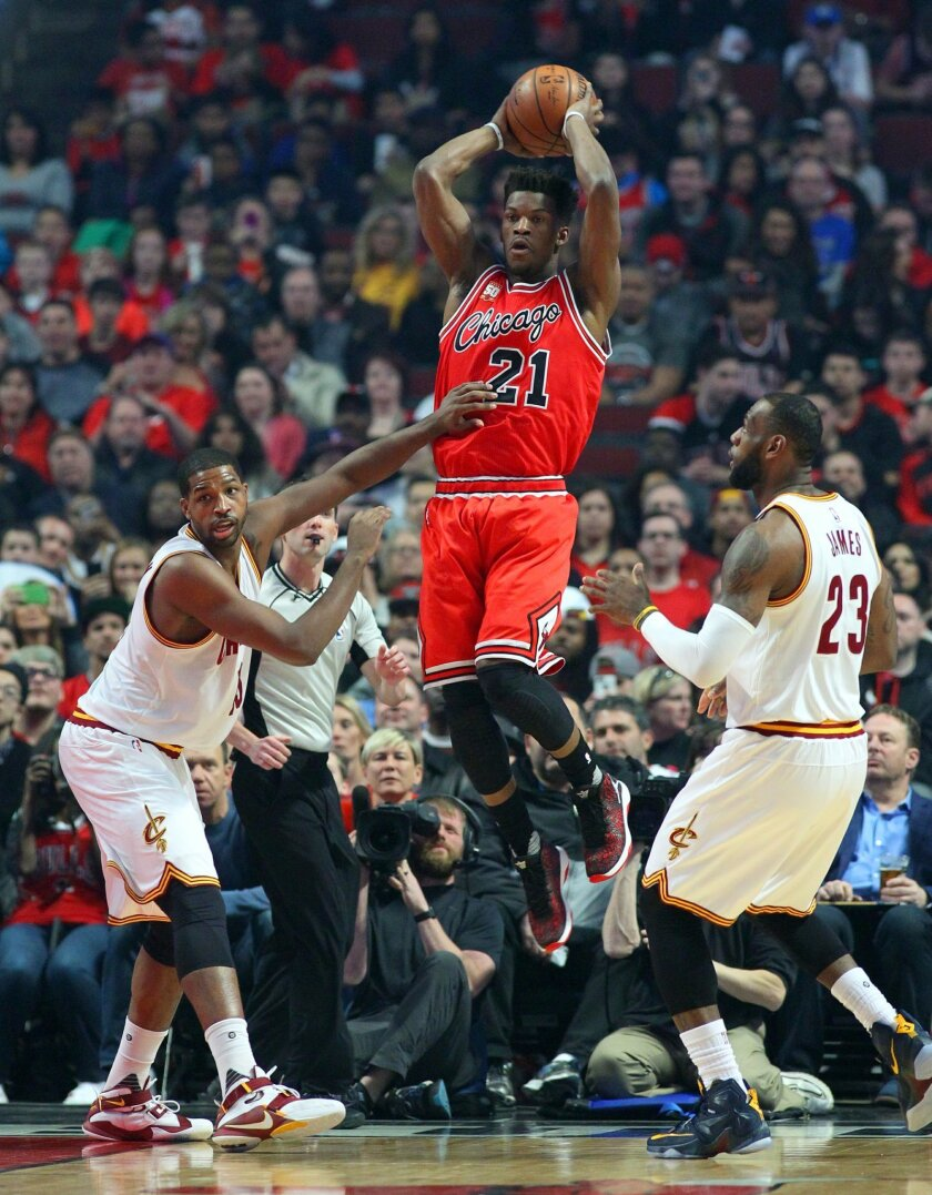 Chicago Bulls guard Jimmy Butler (21) looks to pass between Cleveland Cavaliers center Tristan Thompson (13) and forward LeBron James (23) during the first half of an NBA basketball game in Chicago, on Saturday, April 9, 2016.  (AP Photo/Jeff Haynes)