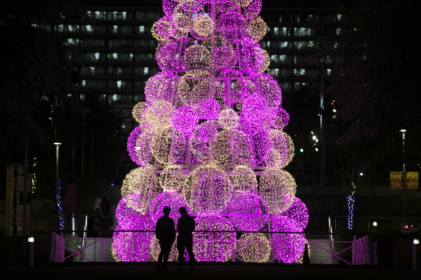 Two people stand in front of a 45-foot-tall Christmas tree at Grand Park Monday, Dec. 17, 2018, in Los Angeles. The tree is part of the Winter Glow light installations at the park created to celebrate the holiday season. (AP Photo/Jae C. Hong)