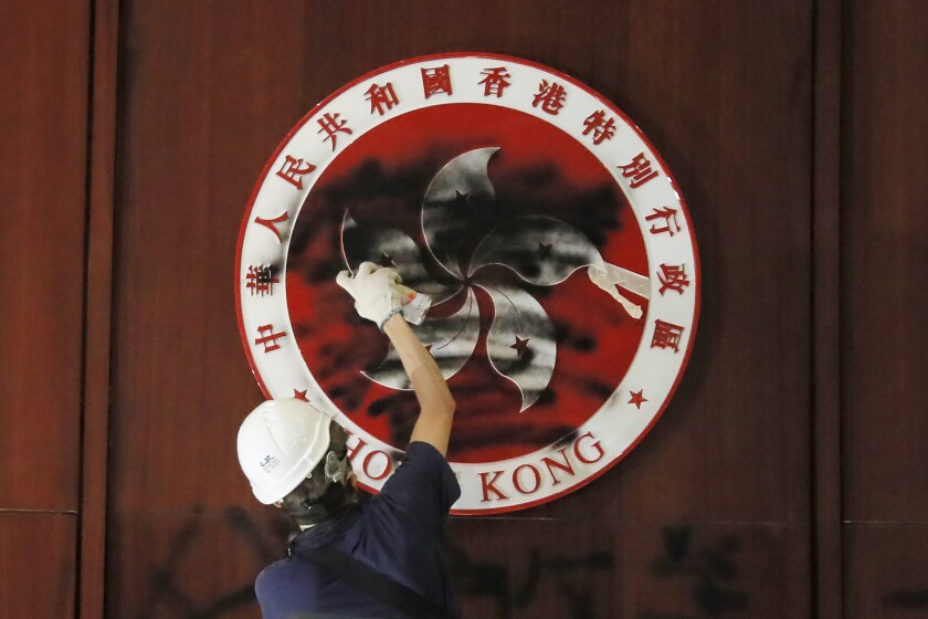A protester defaces the Hong Kong emblem after they broke into the Legislative Council building in Hong Kong, Monday, July 1, 2019. One year ago, a sea of humanity - a million people by some estimates - marched through central Hong Kong on a steamy afternoon. It was the start of what would grow into the longest-lasting and most violent anti-government movement the city has seen since its return to China in 1997. (AP Photo/Kin Cheung, File)