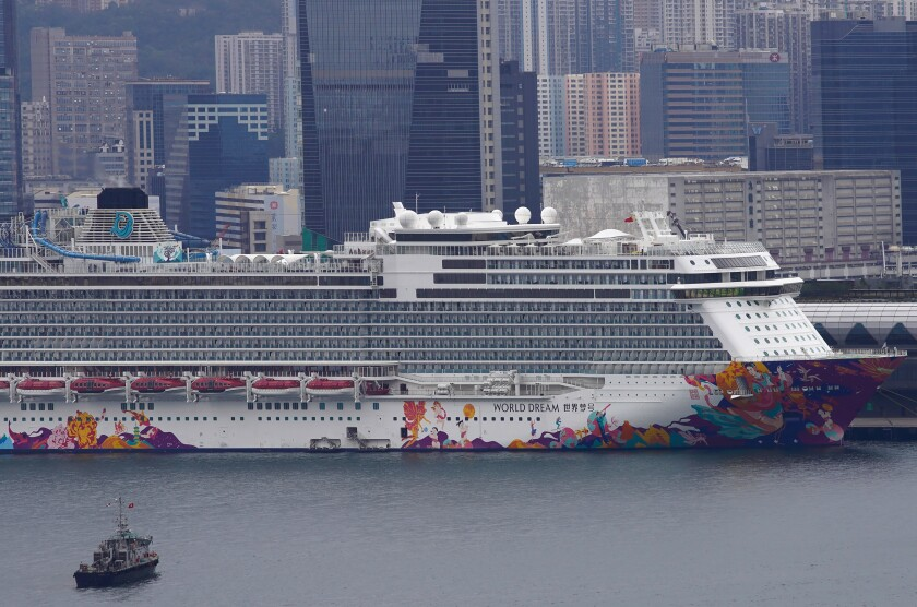 The World Dream cruise ship docked at Kai Tak cruise terminal in Hong Kong, Wednesday, Feb. 5, 2020. A Hong Kong official says more than 3,600 people on board the cruise ship that was turned away from a Taiwanese port will be quarantined until they are checked for a new virus. (AP Photo/Vincent Yu)