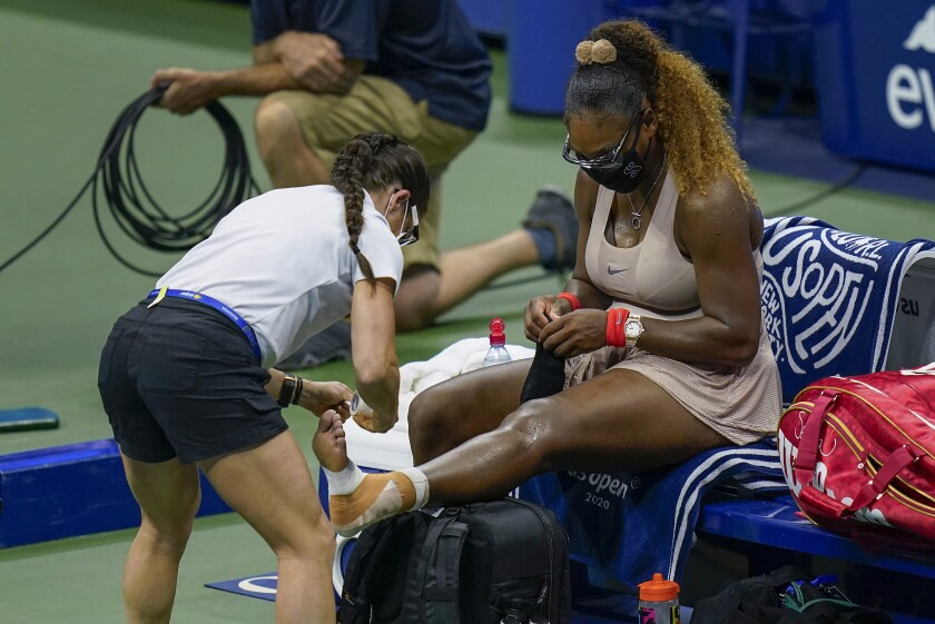 Serena Williams, of the United States, has her ankle taped by a trainer during a medical timeout during a semifinal match of the US Open tennis championships against Victoria Azarenka, of Belarus, Thursday, Sept. 10, 2020, in New York. (AP Photo/Seth Wenig)