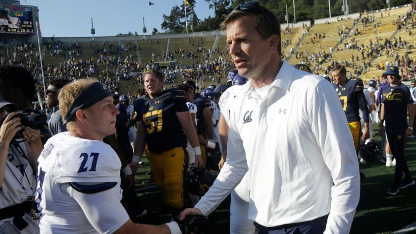 California head coach Justin Wilcox, right, shakes hands with Weber State safety Jantz Arbon after t