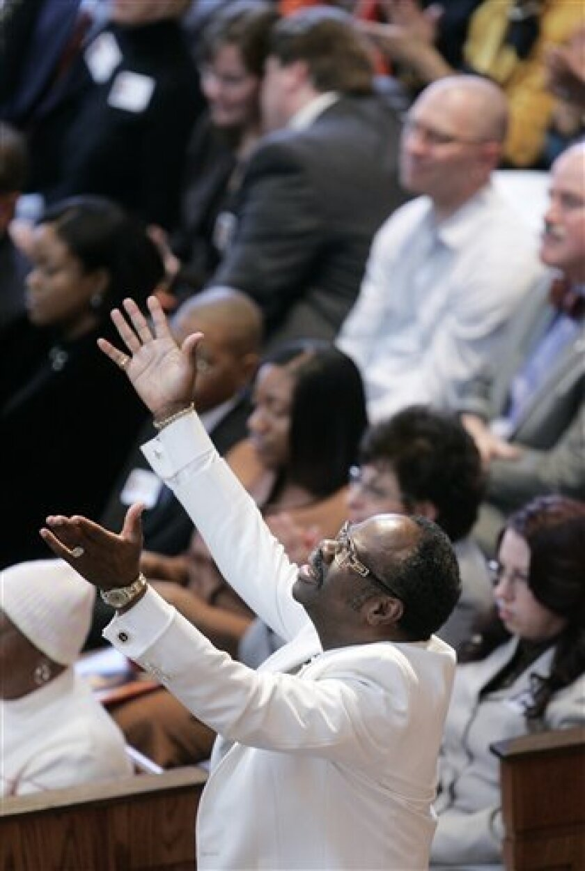 A man holds his arms up during the Martin Luther King Jr., Annual Commemorative Service at Ebenezer Baptist Church in Atlanta Monday, Jan. 19, 2009. (AP Photo/John Bazemore)