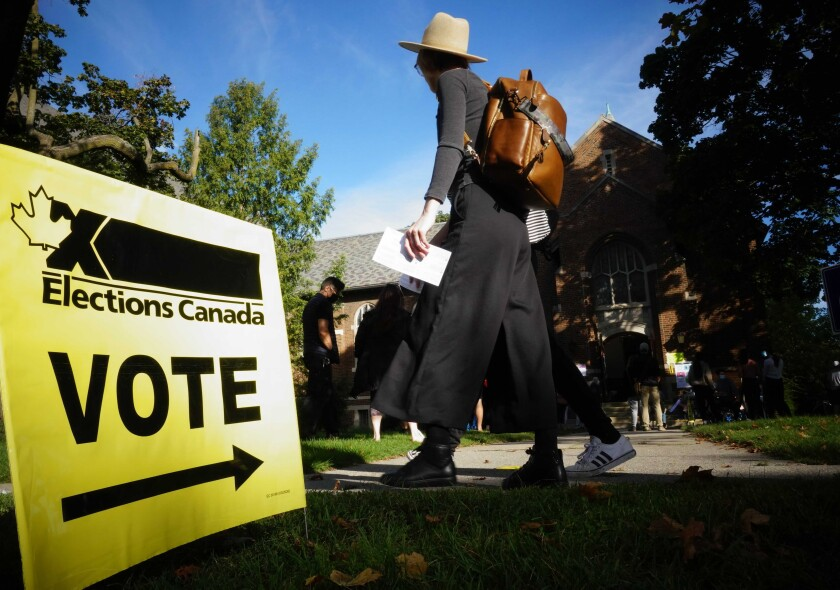 People walk past a lawn sign that says Elections Canada, Vote