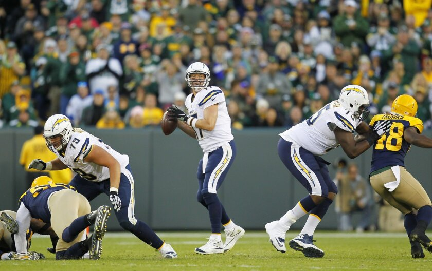 San Diego Chargers quarterback Philip Rivers drops back behind Kenny Wiggins, left, and Chris Hairston, right.   The Packers won 27-20.