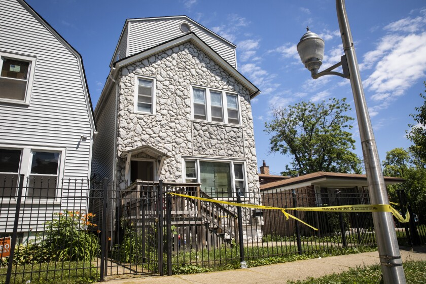 Crime scene tape hangs outside a house where multiple people were shot, some fatally, inside the Englewood building, Tuesday, June 15, 2021. An argument in the house on Chicago's South Side erupted into gunfire early Tuesday. (Ashlee Rezin Garcia/Chicago Sun-Times via AP)