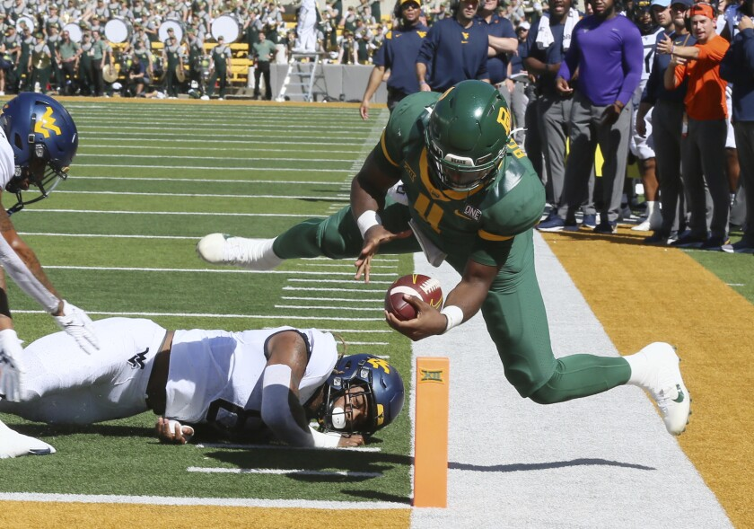 Baylor quarterback Gerry Bohanon is knocked out of bounds short of the goal line as West Virginia linebacker VanDarius Cowan defends in the first half of an NCAA college football game, Saturday, Oct. 9, 2021, in Waco, Texas. He would score on the next play. (Rod Aydelotte/Waco Tribune-Herald via AP)