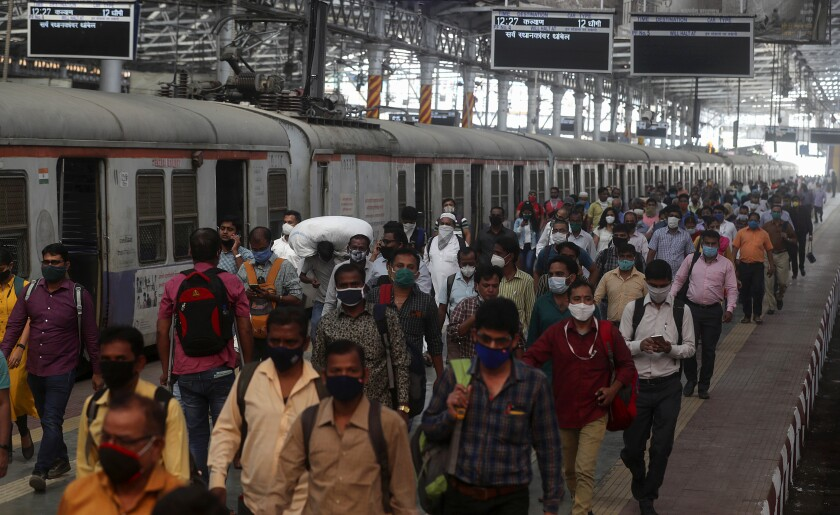 Indian commuters crowd the Chhatrapati Shivaji train Terminus in Mumbai, India, Monday, Feb 1, 2021. India's government on Monday announced it will boost healthcare spend amid the coronavirus pandemic and said it was committed to the development of the financial institutions and shoring up of infrastructure to get the pandemic-ravaged nation back as the world's fastest-growing major economy.(AP Photo/Rafiq Maqbool)