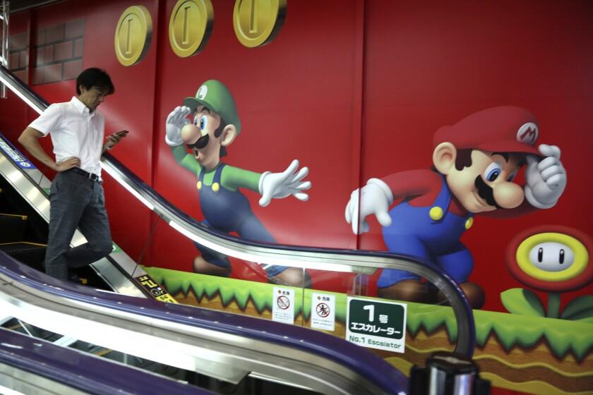 Un cliente pasa por delante de un pared decorada con los personajes del videojuego Super Mario de Nintendo, en una tienda en Tokio, el 13 de julio de 2015. (Foto AP/Koji Sasahara)