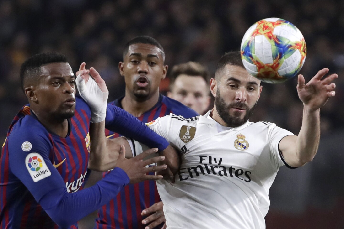 Barcelona defender Nelson Semedo uses his arms to prevent Real forward Karim Benzema from accepting a high ball during the Copa del Rey semifinal first leg soccer match between FC Barcelona and Real Madrid at the Camp Nou stadium in Barcelona, Spain, Wednesday Feb. 6, 2019. (AP Photo/Emilio Morenatti)