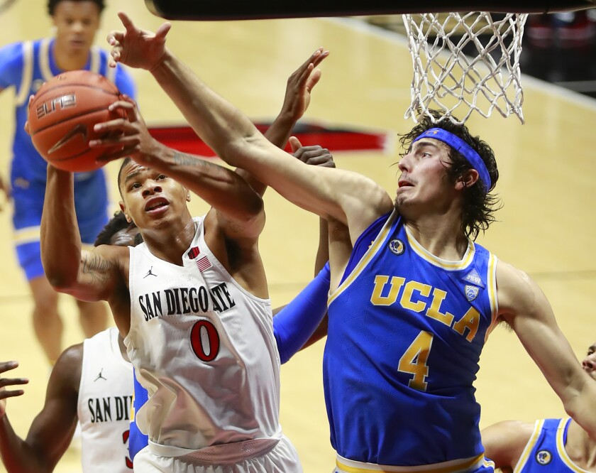 San Diego State's Keshad Johnson grabs a rebound and scores against UCLA's Jamie Jaquez Jr. at Viejas Arena.
