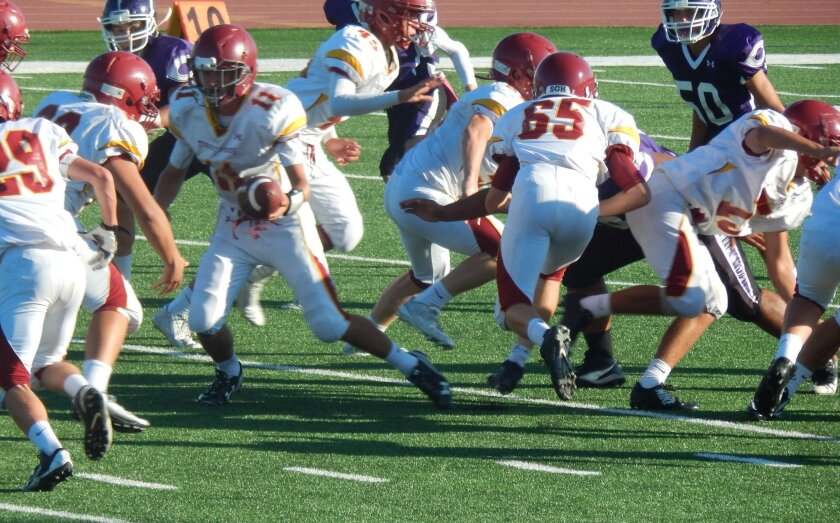 Quarterback Chris Temby hands off to Jadon Cotton. Photo by Walter Bays