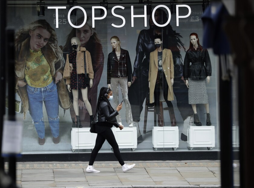 FILE - In this file photo dated Friday, Nov. 20, 2020, a woman wearing a face mask walks past mannequins wearing face masks in the window of a temporarily closed branch of the Topshop women's clothing chain in London. Online retail company ASOS, confirmed Monday Feb. 1, 2021, it has sealed the takeover of Topshop and three other brands from the collapse of the Arcadia retail empire, buying the brand names but not the high street retail space. (AP Photo/Matt Dunham, FILE)