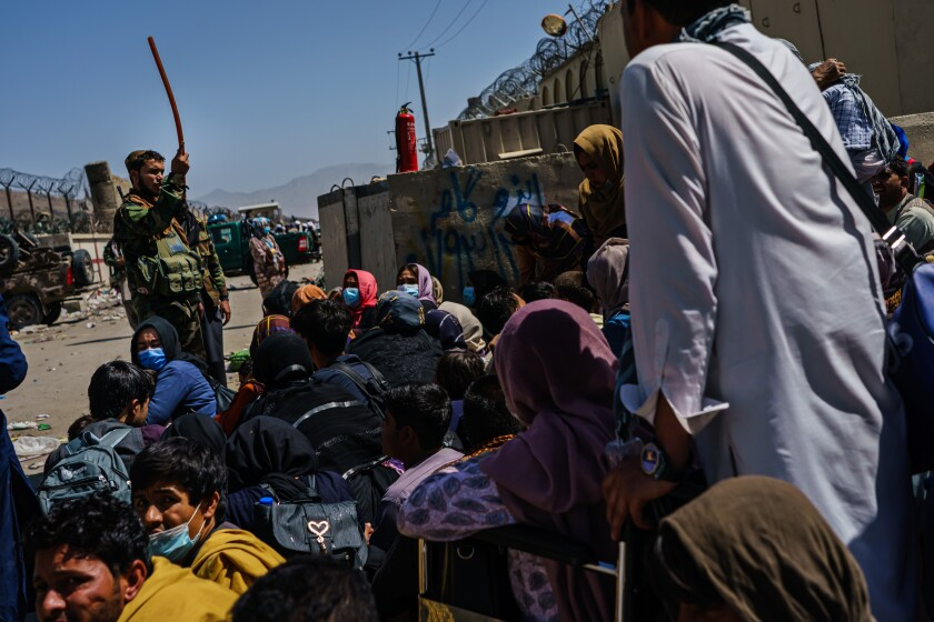 Afghans wait at a Taliban-controlled checkpoint
