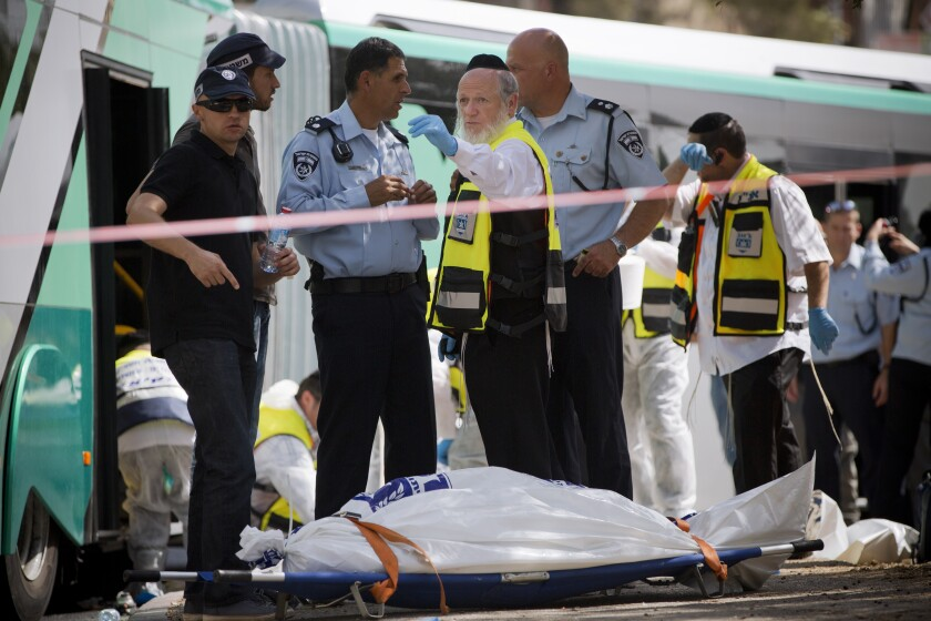 FILE - In this Oct. 13, 2015 file photo, Yehuda Meshi-Zahav, then head of Israel's ZAKA rescue service, center, stands next to the body of an Israeli killed in a shooting by a Palestinian attacker, in Jerusalem. On Sunday, March 14, 2021, the Israeli police announced that the force's major crimes unit, Lahav 433, had opened an investigation into sexual abuse allegations against Meshi-Zahav. In recent days, some 20 people have come forward with claims that he was a savage sexual predator who assaulted men, women and children for years. (AP Photo Oded Balilty, File)