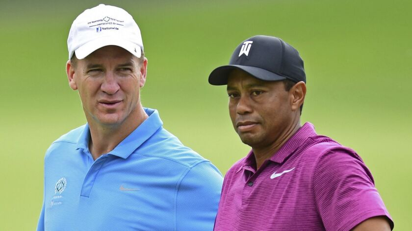 Peyton Manning, left, looks at Tiger Woods on the eleventh hole during the pro-am for the the Memori