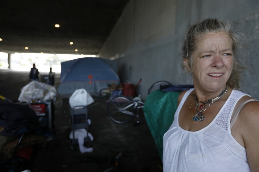 Candy Johnson, 47, stands amid tents on a sidewalk on the Los Angeles-Culver City line at Venice Boulevard, where some homeless people say Culver City police have told them to move to the L.A. side of the street.