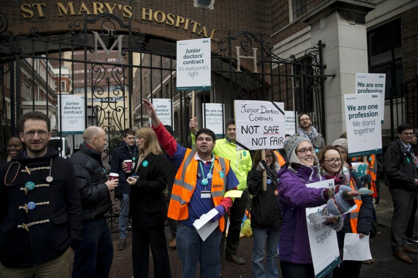 Junior doctors supported by other healthcare workers take part in a 24-hour strike as they stand on a picket line with placards outside St Mary's Hospital, which includes the private wing where the two royal babies were born in recent years, in London, Wednesday, Feb. 10, 2016. Thousands of junior