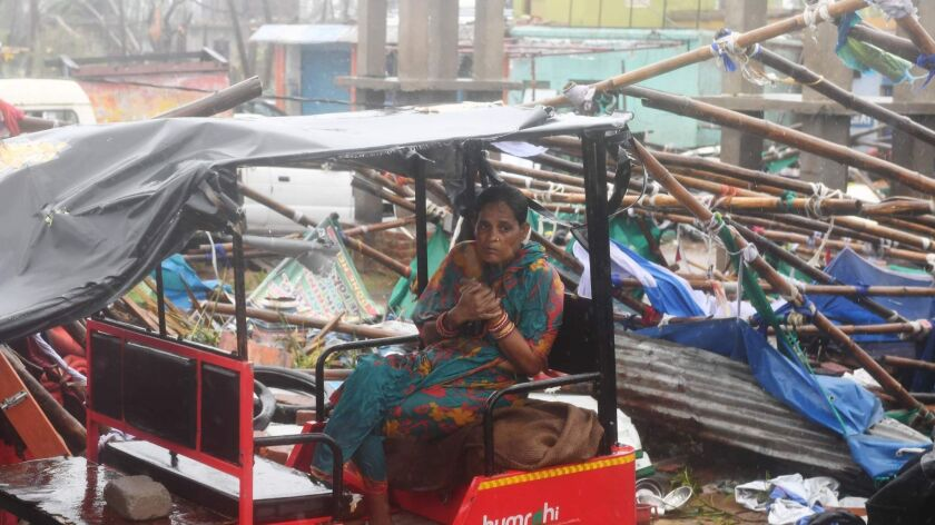 A woman sits in a taxi amid the rubble of structures blown down by Cyclone Fani in Puri in the eastern Indian state of Odisha on May 3, 2019.