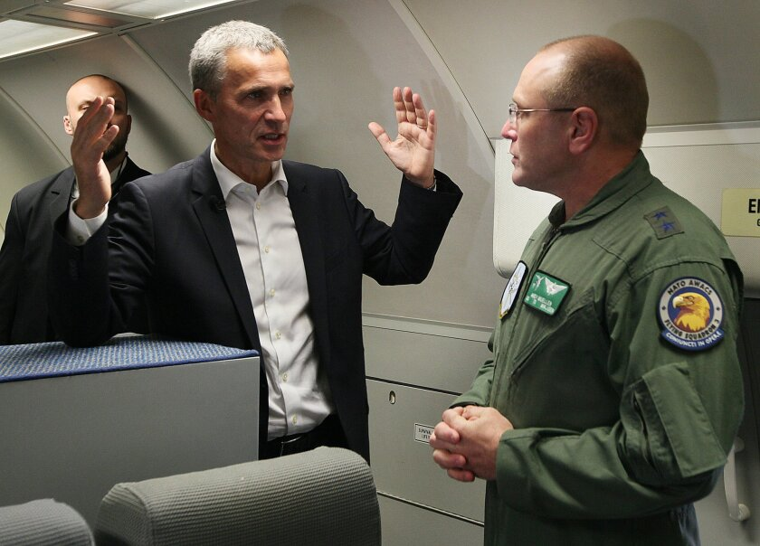 New NATO Secretary General Jens Stoltenberg of Norway, left, talks with Major General Andrew Mueller, right, commander of E-3A component during his visit to the 32 Tactical Air Base in Lask, Poland, Monday, Oct. 6, 2014. Stoltenberg is in Poland on his first foreign trip since starting the job last week, a visit meant to reassure a nervous ally on the alliance's eastern flank. (AP Photo/Czarek Sokolowski)