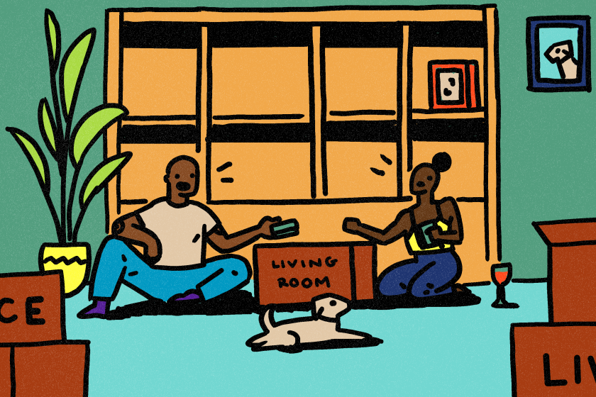 A couple with their dog in front of a bookcase, sitting on the floor and packing things into boxes