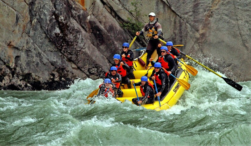 """The Elaho River is less than 50 miles long but lively. Here, guide """"Big Bob"""" Vranich, standing, helps power a raft through a Class-III-plus rapid. The river starts north of Whistler and flows into the Squamish River."""