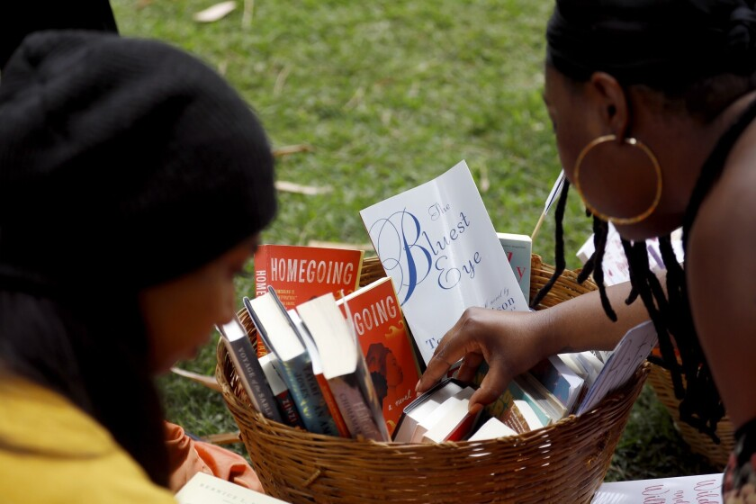 San Marino, CA JUNE 23, 2019: Guests reach into a basket of books by black women authors. Asha Gr