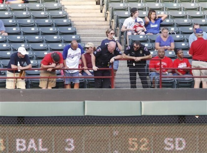 Police and fans look over the railing where a fan fell from the stands during the second inning of a baseball game between the Texas Rangers and the Oakland Athletics, Thursday, July 7, 2011, in Arlington, Texas. (AP Photo/Jeffery Washington)