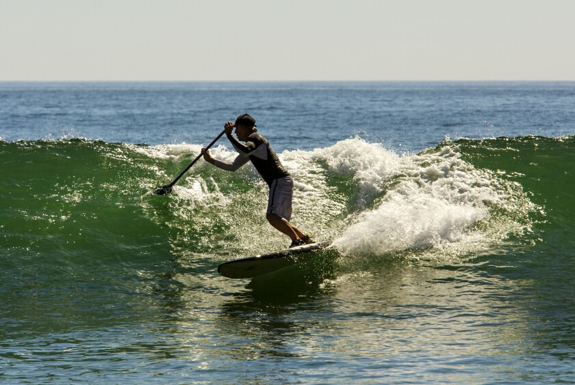 A paddleboarder rides a wave at Topanga State Beach in October 2015. February of 2016 was almost two degrees above the previous record set in 1954.