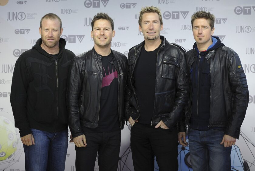 "FILE - In this Aug. 1, 2012 file photo, members of Nickelback pose for photographers as they arrive on the red carpet at the Juno Awards in Ottawa. Twitter has removed President Donald Trump's tweet of a Nickelback meme aimed at former Vice President Joe Biden because of a copyright complaint. The removed post, which featured the group's 2015 music video ""Photograph,"" showed singer Chad Kroeger holding an edited photo of Biden, his son Hunter, a Ukrainian gas executive and another man. A Twitter spokesperson on Wednesday, Oct. 2, 2019, said it responded ""to valid copyright complaints sent to us by a copyright owner or their authorized representatives."" (AP Photo/The Canadian Press, Sean Kilpatrick)"