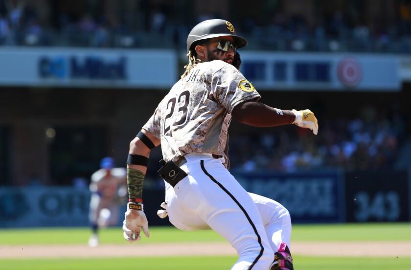 Fernando Tatis Jr. runs to second base after New York Mets pitcher Marcus Stroman made a throwing error