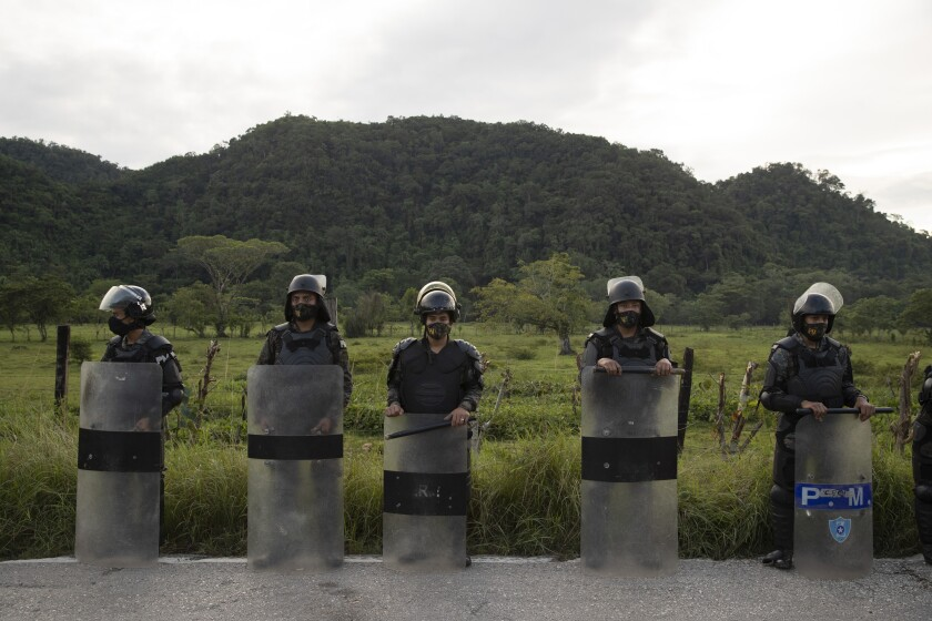 Security forces block Honduran migrants in San Luis Peten, Guatemala, Saturday, Oct. 3, 2020. Early Saturday, hundreds of migrants who had entered Guatemala this week without registering were being bused back to their country's border by authorities after running into a large roadblock. (AP Photo/Moises Castillo)