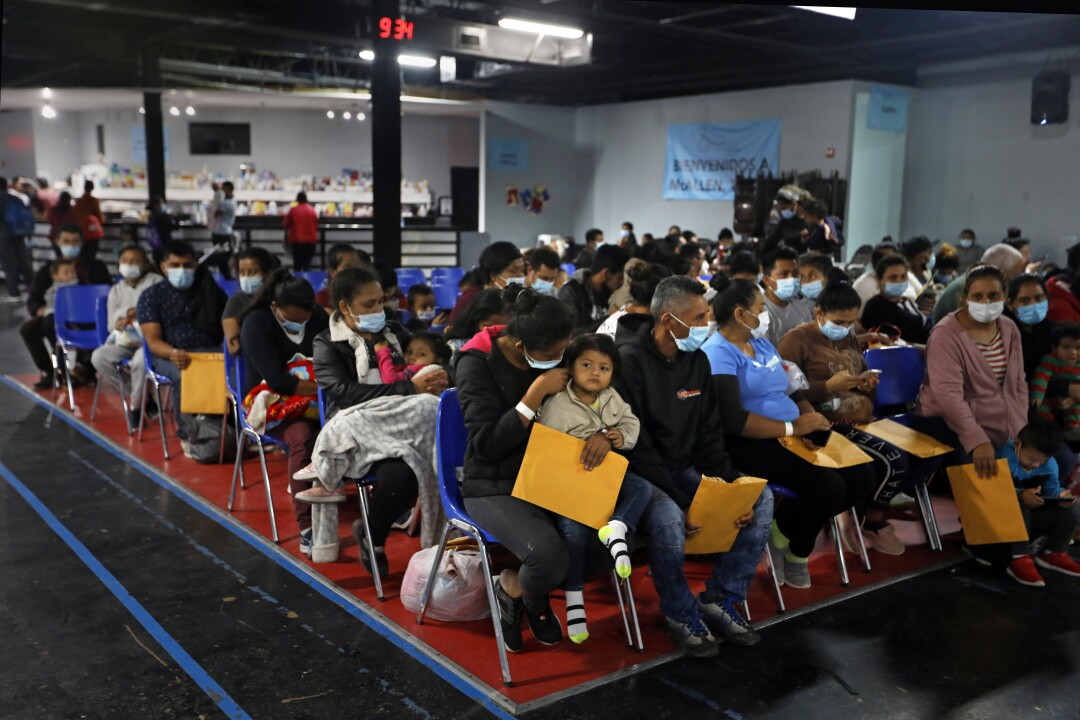 Asylum seekers holding large manila envelopes sit in rows of chairs