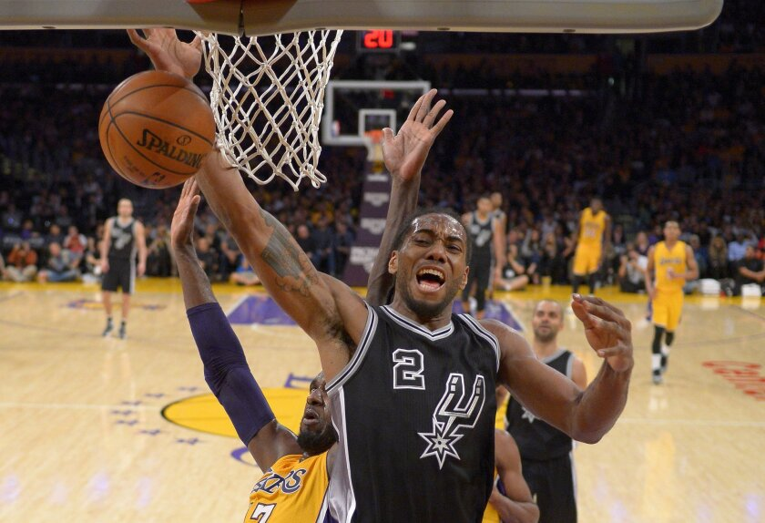 San Antonio Spurs forward Kawhi Leonard, right, loses control of the ball on a shot as Los Angeles Lakers center Roy Hibbert defends during the second half of an NBA basketball game Friday, Jan. 22, 2016, in Los Angeles. The Spurs won 108-95. (AP Photo/Mark J. Terrill)