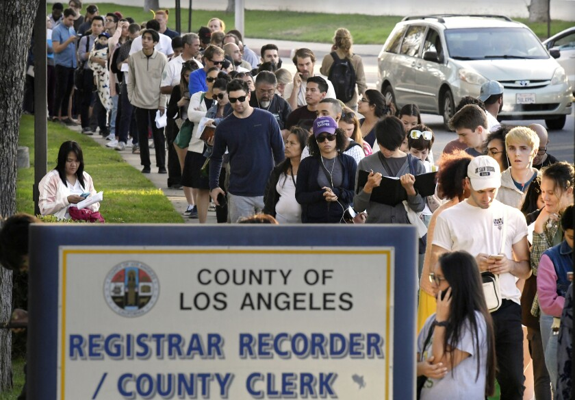 FILE - In this Nov. 6, 2018 file photo potential voters wait in long lines to register and vote at the Los Angeles County Registrar's office in Los Angeles.A pair of propositions on California's November ballot would expand voting rights in California - restoring the vote for parolees and allowing 17-year-olds to vote in primaries if they turn 18 before the general election. (AP Photo/Mark J. Terrill, File)
