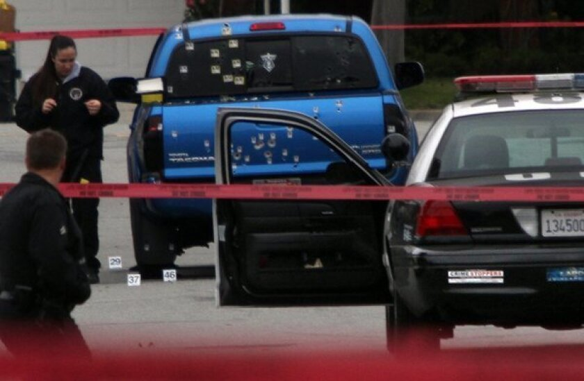 Police investigators work around a blue pickup truck riddled with bullets in the 19500 block of Redbeam Avenue in Torrance after police fired on it on Feb. 7, 2013.