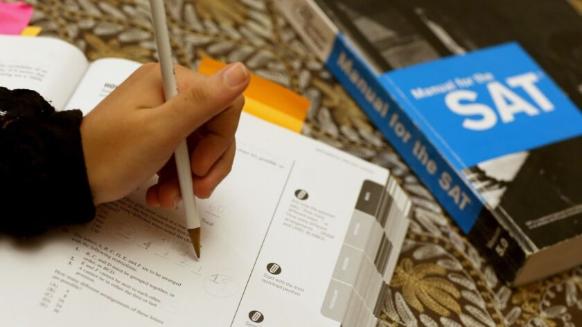 A student uses a test preparation guide to study for the SAT.