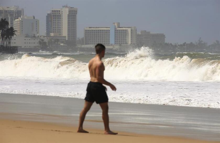 Un hombre pasea frente a unas altas olas el lunes 5 de marzo de 2018, en la playa de Ocean Park en San Juan, Puerto Rico. EFE/Archivo