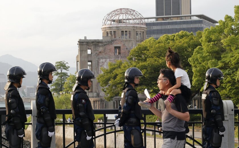 With the Atomic Bomb Dome as a backdrop, passers-by move past riot police near Hiroshima Peace Memorial Museum in Hiroshima, southwestern Japan, Thursday, May 26, 2016. U.S. President Barack Obama is to visit Hiroshima on Friday, May 27 after the Group of Seven summit in central Japan, becoming the