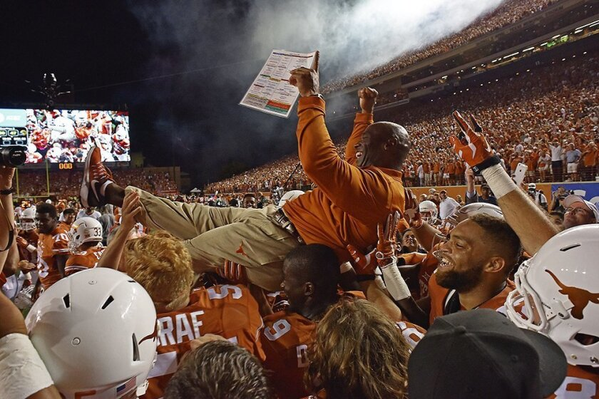 FILE - In this Sept. 4, 2016, file photo, Texas head coach Charlie Strong is carried by players after defeating Notre Dame in double overtime of an NCAA college football game, in Austin, Texas. Texas is ranked for the first time under coach Charlie Strong, coming in at No. 11 in the latest Associat