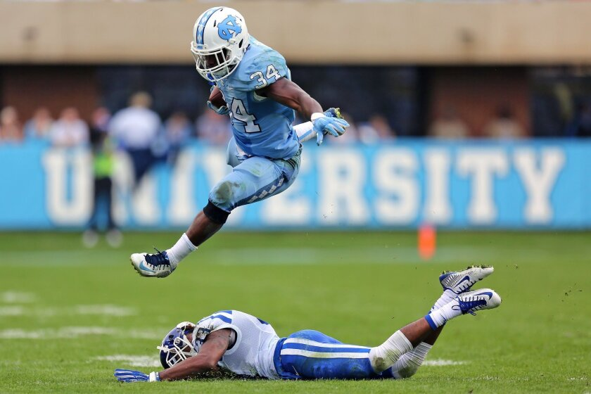North Carolina tailback Elijah Hood, top, leaps over Duke safety Deondre Singleton while running the ball during an NCAA college football game, Saturday, Nov. 7, 2015, at Kenan Memorial Stadium in Chapel Hill, N.C. (Adam Jennings/The Rocky Mount Telegram via AP) MANDATORY CREDIT