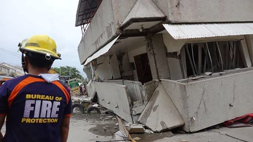 A rescuer is pictured near a collapsed building in the southern Philippines following an earthquake on Sunday. At least five people died in the magnitude 6.9 quake that struck Davao del Sur province's Padada town and outlying rural towns, cities and provinces.